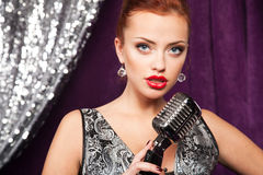 Woman with microphone. A young woman posing with retro microphone Stock Image