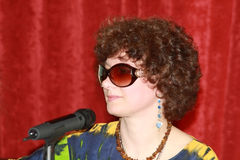 Woman with a microphone. Woman in dark glasses with a microphone, on red background Stock Photo