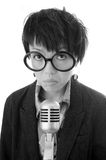 Woman and microphone. A black & white image of a cute woman with frowning expression in front of a microphone Royalty Free Stock Image