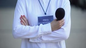 Woman with microphone and press accreditation badge, media pass for journalist. Stock footage stock footage