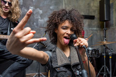 Woman with microphone showing rock sign in studio Stock Photos