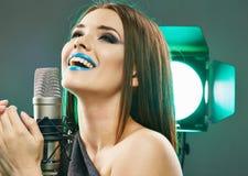 Woman microphone singing. Beauty model soun studio. Posing Royalty Free Stock Images
