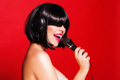 Woman with microphone singing on headphones and Stock Photography