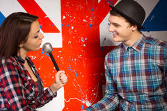 Woman with Microphone Talking To Man. Close up Young Woman with Microphone Talking To Smiling Man in Front Huge Britain Flag Print Stock Images