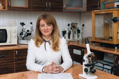 Woman with microscope at lab. Caucasian woman with microscope at laboratory Royalty Free Stock Image