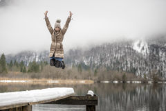 Woman in mid-air jumping near lake. Single excited woman wearing coat and hat jumping in mid-air on snowy pier with cloud covered mountain in background royalty free stock photos