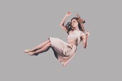 Woman in mid-air. Studio shot of attractive young woman hovering in air Stock Photos