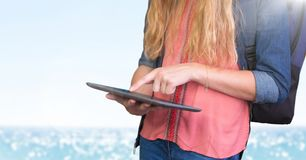 Woman mid section with backpack and tablet against blurry water and flare Stock Photo