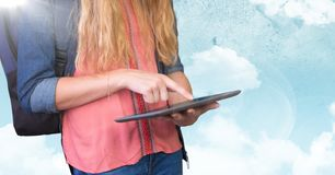 Woman mid section with backpack and tablet against sky and flare Stock Photos