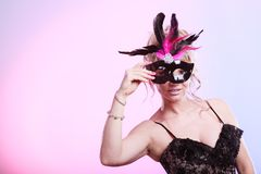 Woman middle aged holds carnival mask. stock photos