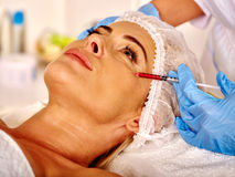 Woman middle-aged in spa salon with beautician. Female giving botox injections. Stock Photo