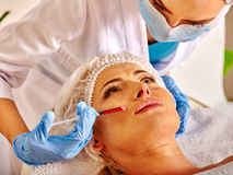Woman middle-aged in spa salon with beautician. Female giving botox injections. stock images