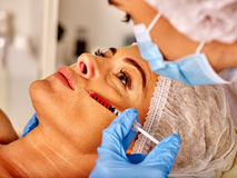 Woman middle-aged into spa salon with beautician. Female giving botox injections. Stock Photo