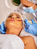 Woman middle-aged in spa salon with beautician. Female giving injections. Stock Image