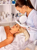 Woman middle-aged in spa salon with cosmetic lamp Royalty Free Stock Photography
