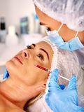 Woman middle-aged in spa salon giving botox injections. Royalty Free Stock Photos
