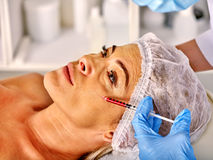 Woman middle-aged in spa salon  giving botox Stock Photography
