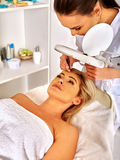 Woman middle-aged in spa salon. Tweezing eyebrow by beautician. Stock Images