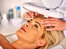 Woman middle-aged in spa salon. Tweezing eyebrow by beautician. Stock Photo