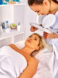 Woman middle-aged in spa salon. Tweezing eyebrow Royalty Free Stock Image