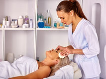 Woman middle-aged take face cleaning in spa salon. Royalty Free Stock Photos