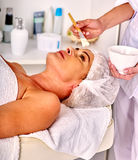 Woman middle-aged take face massage in spa salon. Royalty Free Stock Photography