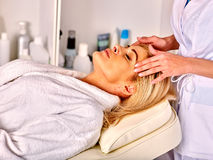 Woman middle-aged take face massage in spa salon Royalty Free Stock Photo
