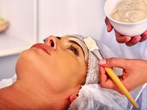 Woman middle-aged take face massage in spa salon. Royalty Free Stock Image