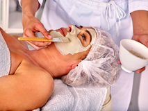 Woman middle-aged take face massage in spa salon. Royalty Free Stock Images