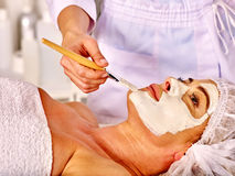 Woman middle-aged take face massage in spa salon Stock Images