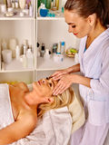 Woman middle-aged take face massage in spa salon. Royalty Free Stock Photos