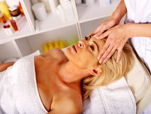 Woman middle-aged take face massage in spa salon. Royalty Free Stock Photo