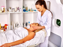Woman middle-aged take face massage in spa salon Stock Image
