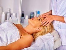 Woman middle-aged take face massage in spa salon. Stock Image