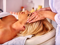 Woman middle-aged take face massage in spa salon. Stock Images