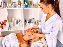 Woman middle-aged take face massage in spa salon Royalty Free Stock Photography
