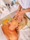 Woman middle-aged take face massage in spa salon. Stock Photography
