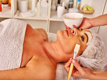 Woman middle-aged take facial and neck anti-aging clay mask in spa salon. Stock Image