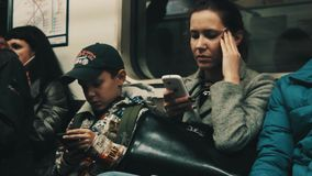 Woman with migraine and boy in cap using smartphones sitting in metro train stock video