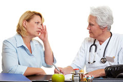 Woman with migraine at doctor. Women with migraine at an elderly doctor Royalty Free Stock Photo