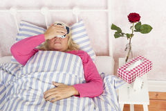 Woman with migraine lying in bed. Ill woman in pink pyjama with headache, tissues and a rose lying in bed with washcloth Royalty Free Stock Photography