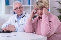 Woman with migraine. Senior women with migraine in doctor's office Stock Image