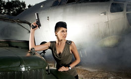 A woman in military clothes posing near a plane stock image