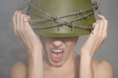 Woman in military helmet with barbed wire screams Royalty Free Stock Photography