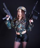 Woman in the military uniform with assault rifles Stock Images