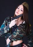 Woman in the military uniform with a gun Royalty Free Stock Image