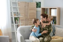 Woman in military uniform with her children on sofa stock photography