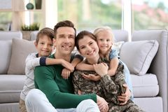 Woman in military uniform with her family. At home royalty free stock images