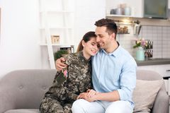 Woman in military uniform with husband on sofa at home. Woman in military uniform with her husband on sofa at home royalty free stock images