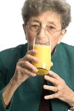 Woman with milk. Ooh a nice glass of orange juice for a pretty woman senior royalty free stock image